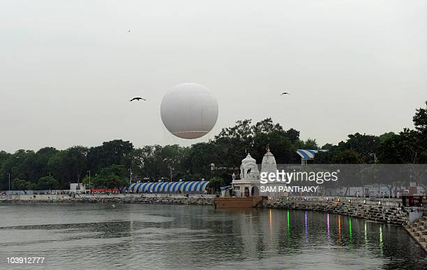 Onlookers watch as a tethered helium balloon is sent up for its test run in Ahmedabad on September 8 2010 India�s first ever tethered helium balloon...