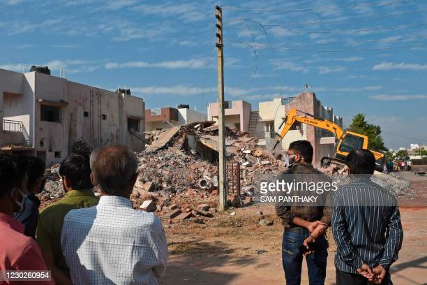 Onlookers watch as an excavator works amid the debris of two residential bungalows that collapsed after a gaseous blast at Kalol town in Gandhinagar...