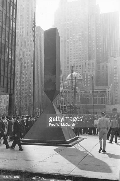 Onlookers watch as Barnett Newman's 'Broken Obelisk' sculpture is erected in the plaza of the Seagram Building New York New York September 27 1967...