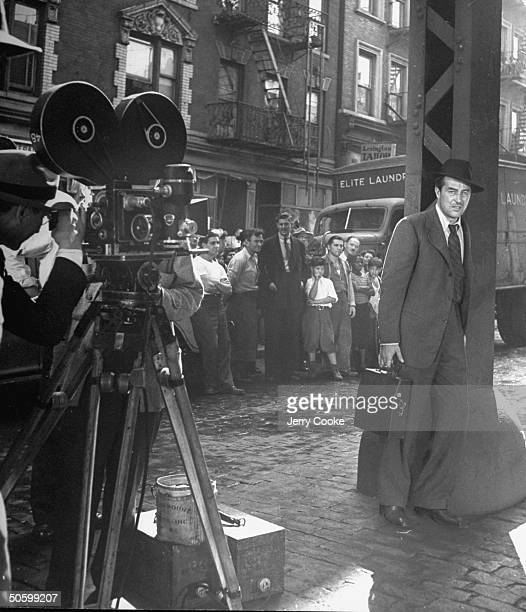 Onlookers watch as camera captures Welshborn actor Ray Milland as he carries a typewriter and stands under the 3rd Avenue elevated train tracks...