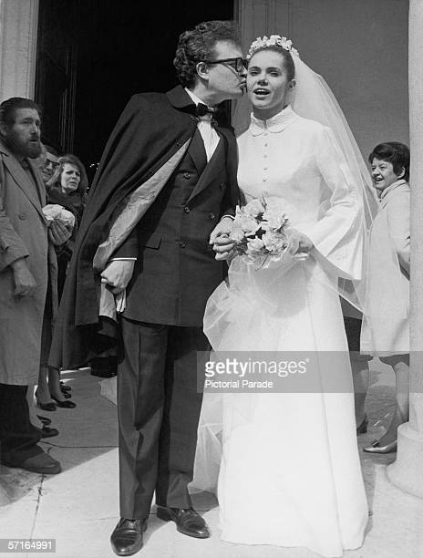 Onlookers watch as French singer and actor Patrick Font kisses his new bride French poetess Minou Drouet outside the SainteMarie des Batignolles...