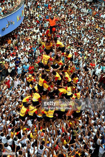 Onlookers watch as Hindu devotees form a human pyramid during the 'Dahihandi' festival to celebrate Janmashtami the birthday of Hindu God Lord...