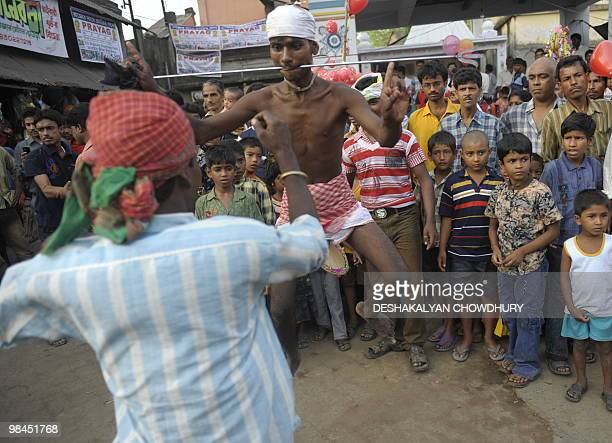 Onlookers watch as Indian Hindu devotees dance with their tongues pierced with metal rods during the ritual of Shiva Gajan at a village in Bainan...