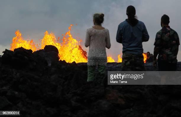 Onlookers watch as lava from a Kilauea volcano fissure erupts in Leilani Estates on Hawaii's Big Island on May 26 2018 in Pahoa Hawaii The Big Island...
