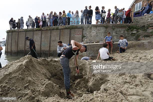 Onlookers watch as people search a beach in Folkestone southeast England on August 29 2014 for gold bullion buried there by German artist Michael...
