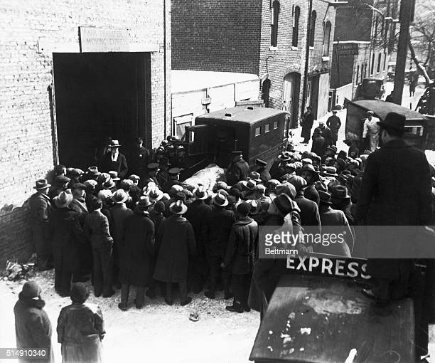 Onlookers watch as police remove the bodies of the victims of an execution style murder from the scene at 2122 North Clark Street in Chicago The...