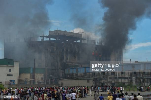 Onlookers watch as smoke bellows from a massive fire that broke out a day before in a beverage and food factory in Rupganj in the district...