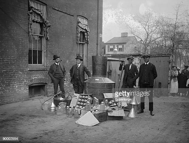 Onlookers watch as suited men stand in front of a large copper kettle still for making illegal liquor with boxes of bottles and funnels spread before...