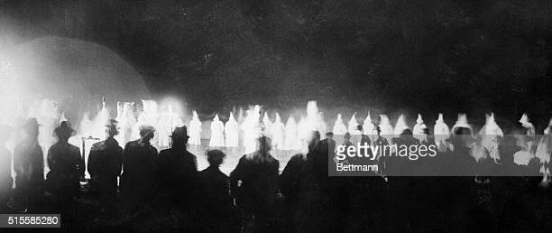Onlookers watch as the Ku Klux Klan initiates new members at a Miami golf course.