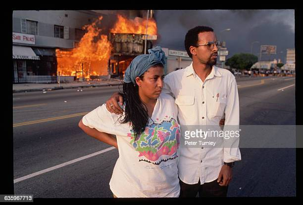 Onlookers watch buildings burn and smoke clouds fill the LA skies as a result of the 1992 riots