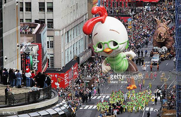 Onlookers watch from a balcony as a Chicken Little balloon floats down Broadway during the 78th Annual Macy's Thanksgiving Day Parade November 25...