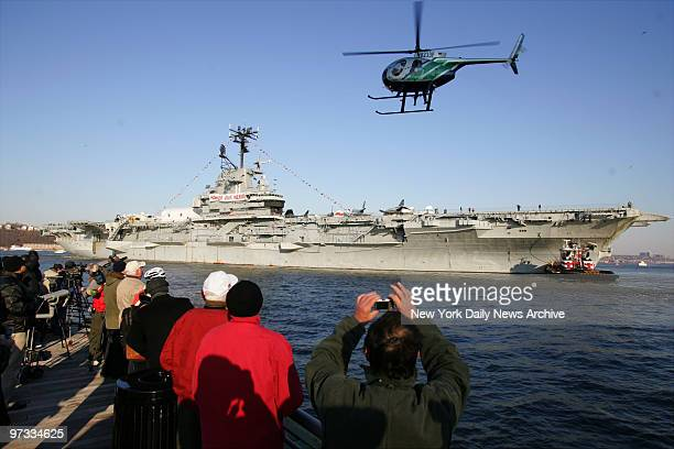 Onlookers watch from a nearby pier as tug boats pull the USS Intrepid away from Pier 86 on the West Side of Manhattan and down the Hudson River to...
