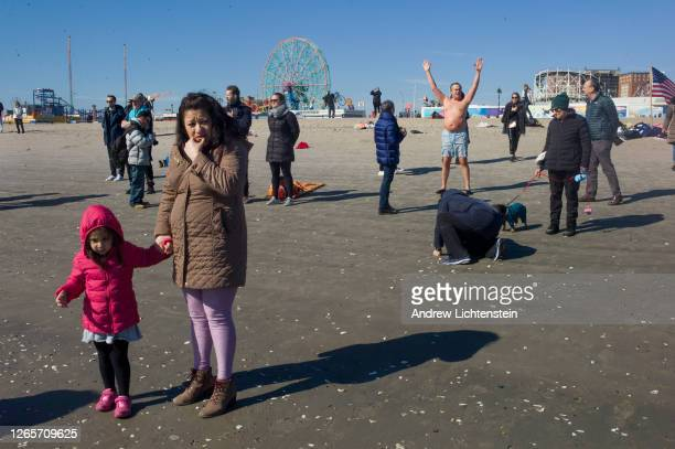 Onlookers watch members of the Polar Bear Club, swimmers who dive into the ocean during the winter months, jump into the ocean on February 23, 2020...
