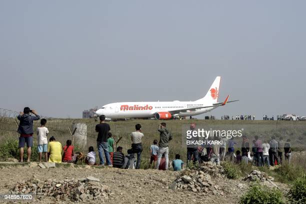 Onlookers watch Nepali workers trying to bring a Malaysian airliner back onto the runway at the international airport in Kathmandu on April 20 after...