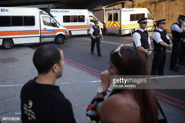 Onlookers watch proceedings at the security cordon at the scene in Finsbury Park area of north London after a vehichle hit pedestrians on June 19...