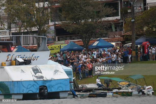 CORRECTION Onlookers watch rescue efforts after the tourist boat Almirante sank in the Reservoir of Penol in Guatape municipality in Antioquia on...