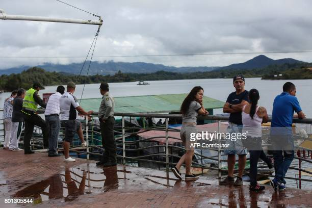 Onlookers watch rescue efforts after the tourist boat 'Almirante' sank in the Reservoir of Penol in Guatape municipality in Antioquia northwestern...