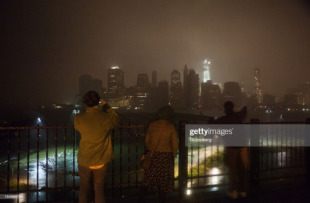 Onlookers watch while flood waters cover a promenade in Brooklyn as numerous buildings in Lower Manhattan, background, stand in darkness in New York, U.S., on Monday, Oct. 29, 2012. Hurricane Sandy, the Atlantic's Ocean's biggest-ever tropical storm, barreled toward southern New Jersey after bringing a region with 60 million residents to a virtual standstill and upending the U.S. presidential race eight days before Election Day. Photograph: Victor J. Blue/Bloomberg via Getty Images
