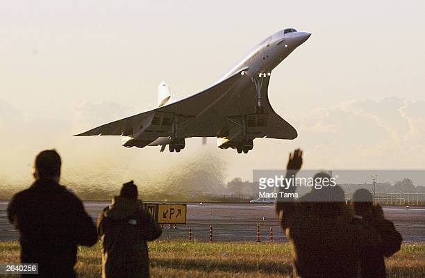 Onlookers wave as the last-ever Concorde passenger flight takes off from John F. Kennedy International Airport en route to London October 24, 2003 in...