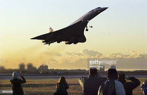 Onlookers wave as the lastever Concorde passenger flight takes off from John F Kennedy International Airport en route to London October 24 2003 in...