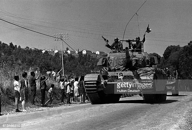 Onlookers wave to soldiers on a tank in a military convoy as they advance into Syria