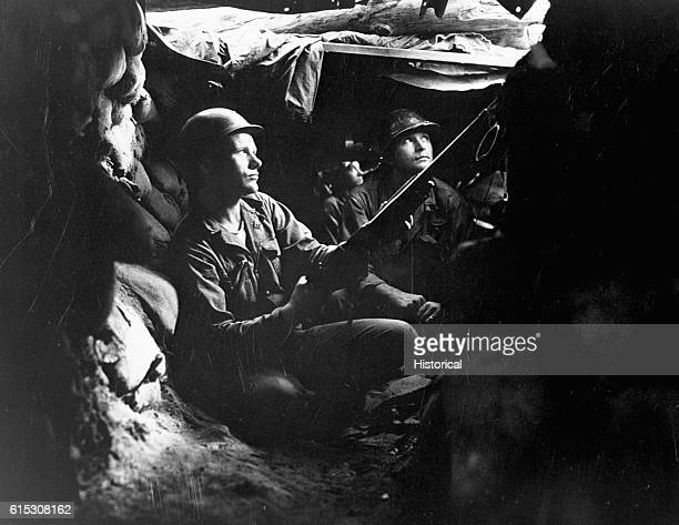 Only 40 yards from the enemy infantrymen of the 27th Infantry Regiment take advantage of cover and concealment in tunnel positions near Heartbreak...