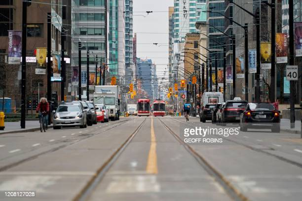 Only a few vehicles line the streets of downtown Toronto, Ontario on March 24, 2020. - The province of Ontario has set a deadline of midnight Tuesday...