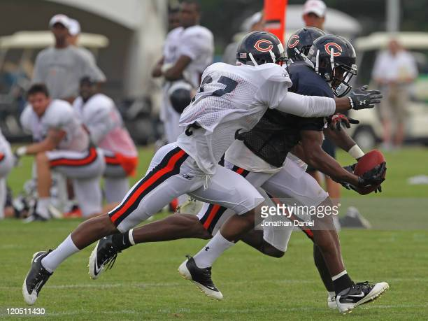 Onrea Jones of the Chicago Bears tries to catch a pass under pressure from Anthony Walters and Zack Bowman during a summer training camp practice at...