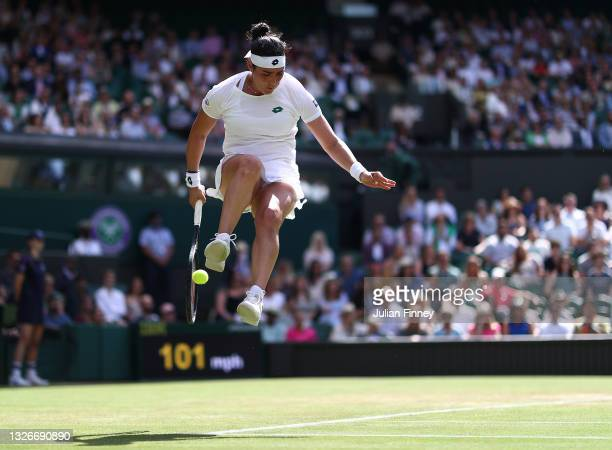 Ons Jabeur of Tunisia jumps in the air as she plays a forehand behind her back during her Ladies Singles Third Round match against Garbine Muguruza...