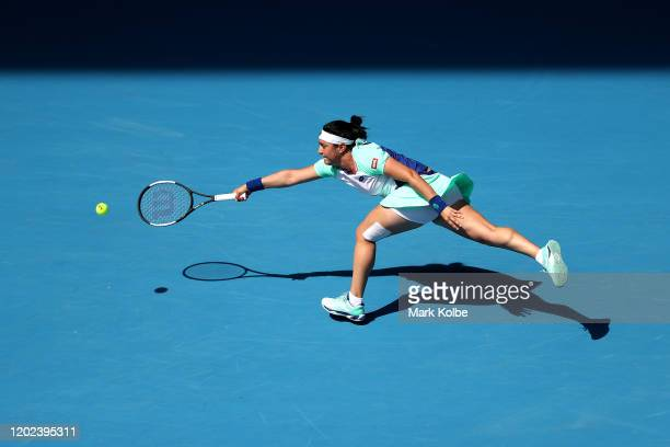 Ons Jabeur of Tunisia stretches to play a forehand during her Women's Singles Quarterfinal match against Sofia Kenin of the United States on day nine...