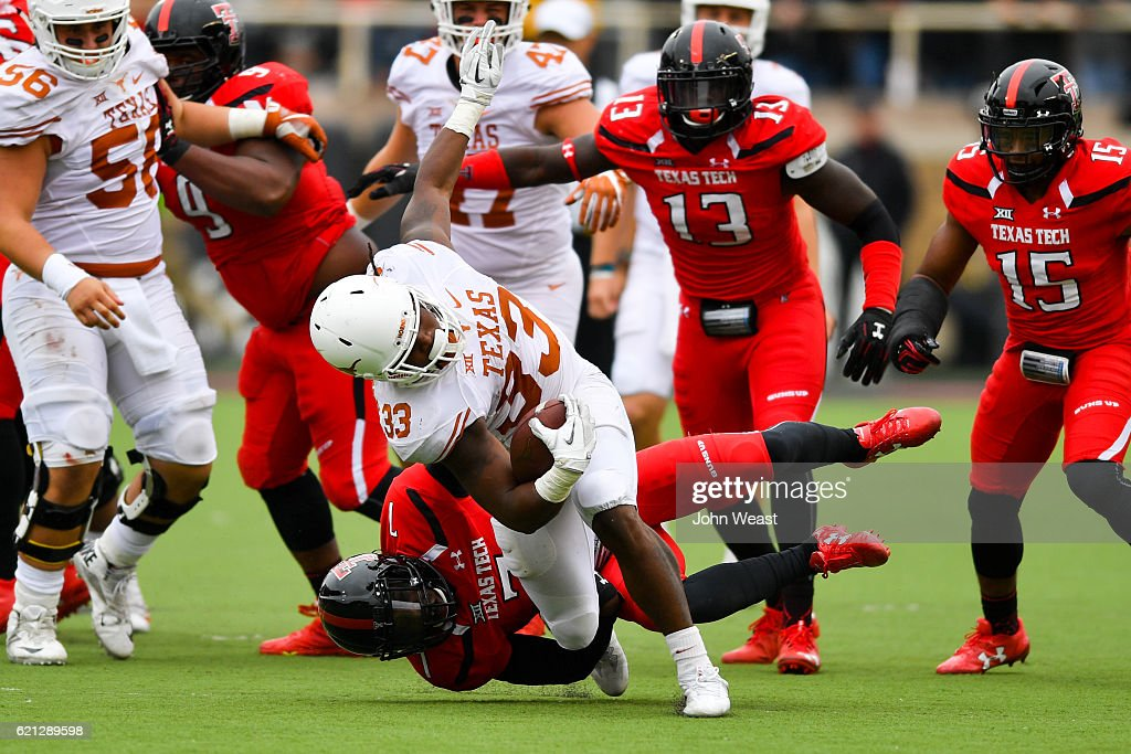 D'Onta Foreman #33 of the Texas Longhorns is brought down by Jah'Shawn Johnson #7 of the Texas Tech Red Raiders during the game on November 5, 2016 at AT&T Jones Stadium in Lubbock, Texas. Texas defeated Texas Tech 45-37.