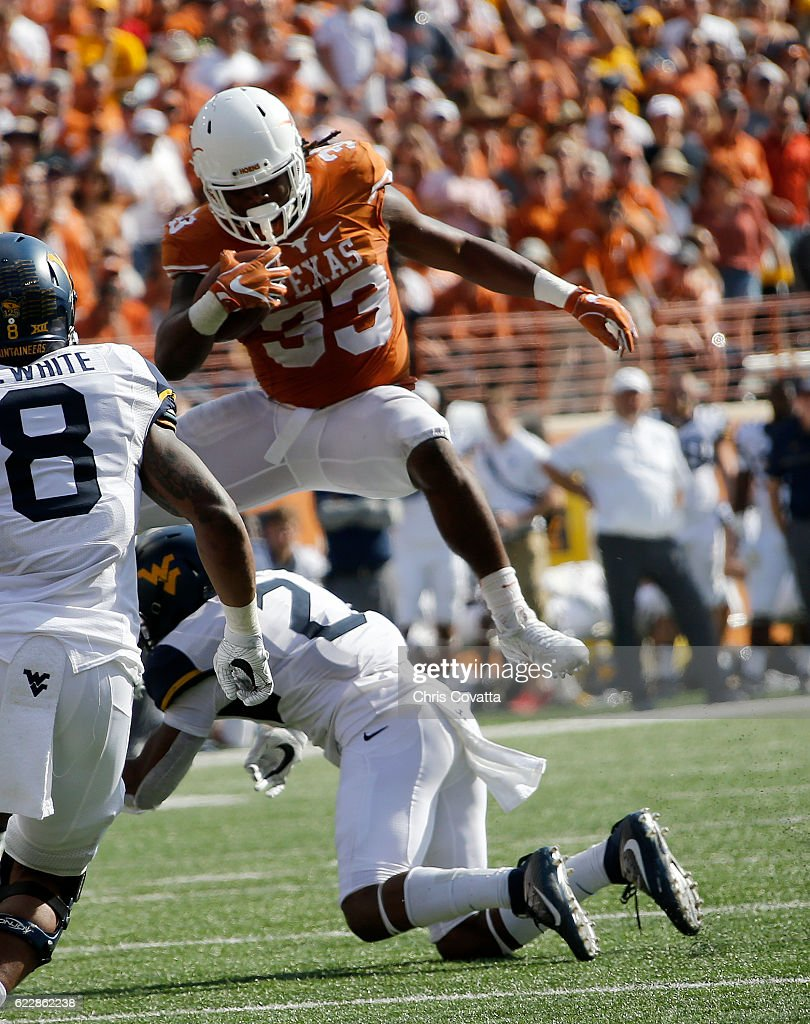 D'Onta Foreman #33 of the Texas Longhorns leaps over Jeremy Tyler #2 of the West Virginia Mountaineers at Darrell K Royal -Texas Memorial Stadium on November 12, 2016 in Austin. Texas.