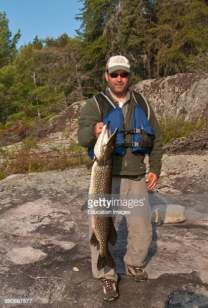 Ontario Quetico Park Lake Kawnipi wilderness Man with 18 inch Northern Pike
