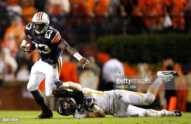 Onterio McCalebb of the Auburn Tigers breaks a tackle by Pat Lazear of the West Virginia Mountaineers at JordanHare Stadium on September 19 2009 in...