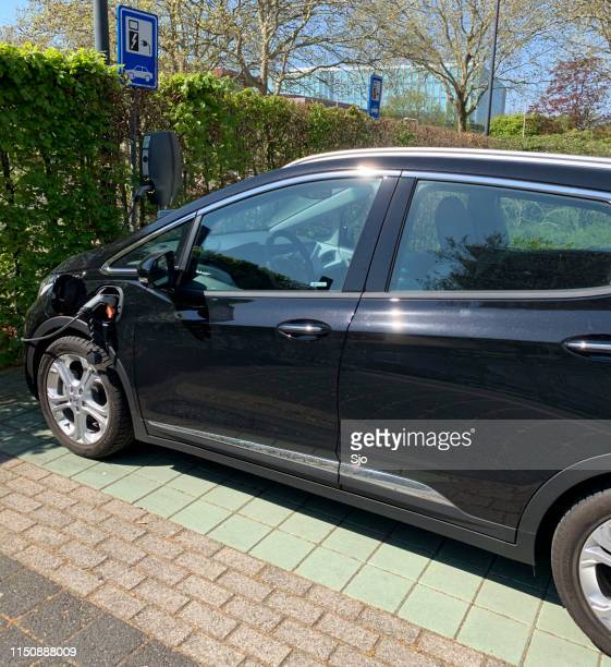 Opel Ampera-e electric car parked next to an electric vehicle charging station