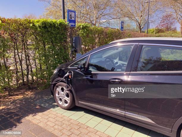 """opel ampera-e elektrische auto geparkeerd naast een oplaadstation voor elektrische voertuigen - """"sjoerd van der wal"""" or """"sjo"""" stockfoto's en -beelden"""
