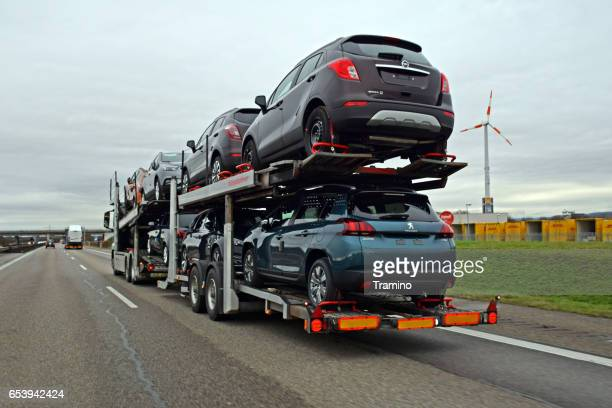 opel and peugeot cars on the same car transporter - car transporter stock photos and pictures