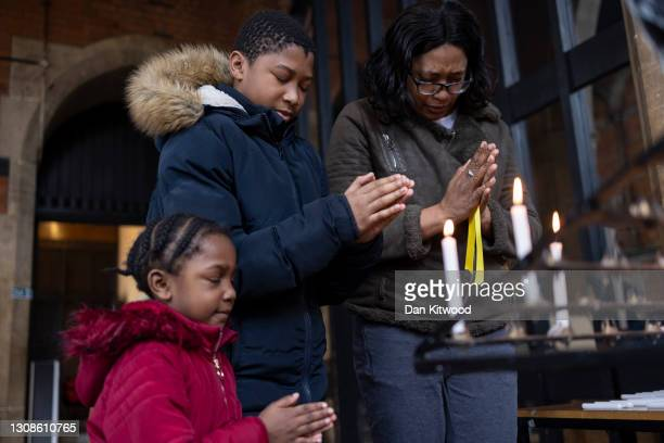 Opel Connolly with her two children, Angel and Sean light a candle of remembrance during a small service at St Catherine's Church on March 23, 2021...