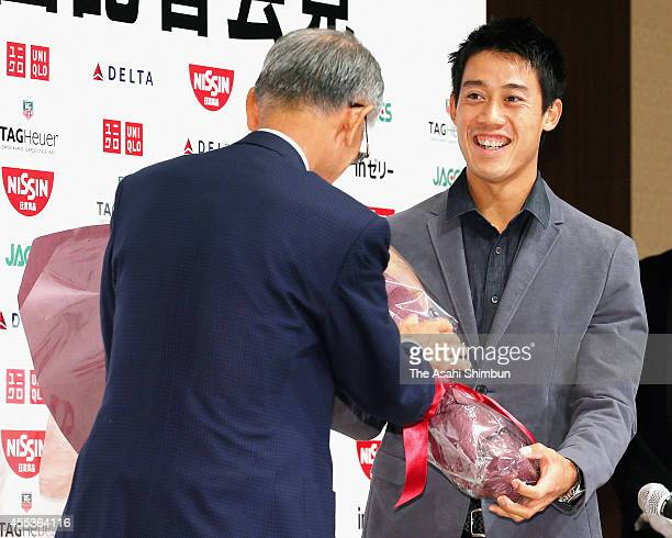 Open 2014 runnerup Kei Nishikori receives a flower bunch from the Japan Tennis Association President Nobuo Kuroyanagi during a press conference upon...