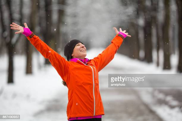 Open Arms - woman enjoying first snow in winter