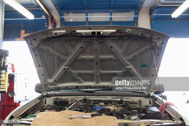 Open automobile hood in repair shop