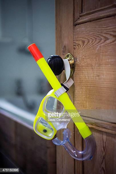 Open bathroom door with hanging snorkel and goggles