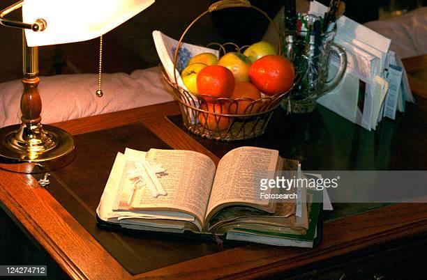 Open bible and fruit basket on desk