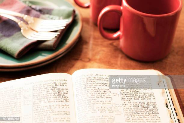 Open Bible and morning coffee on breakfast table.