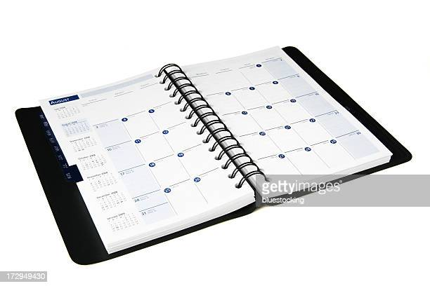 Open black daily planner with calendar isolated on white