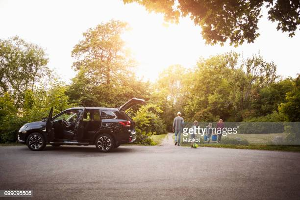 open black electric car with family walking in park - four people in car stock pictures, royalty-free photos & images