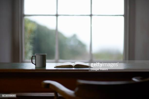 Open book and hot drink on traditional writing desk.