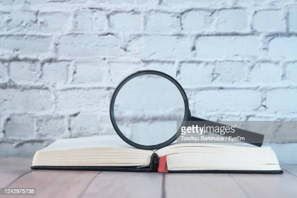 open book and magnifying glass on table - dictionary stock pictures, royalty-free photos & images