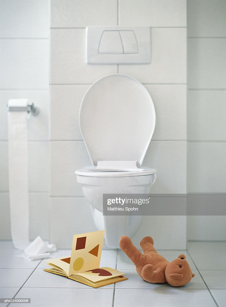 Open book and teddy bear on floor in front of toilet. : Stock Photo