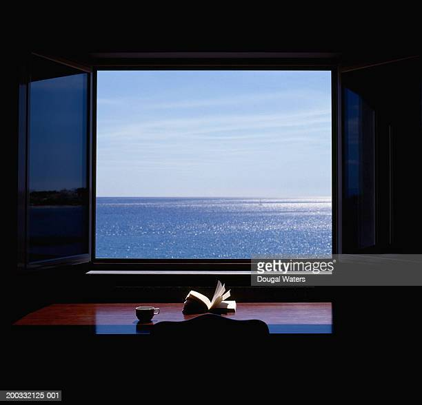 open book by window overlooking sea - dougal waters stock pictures, royalty-free photos & images